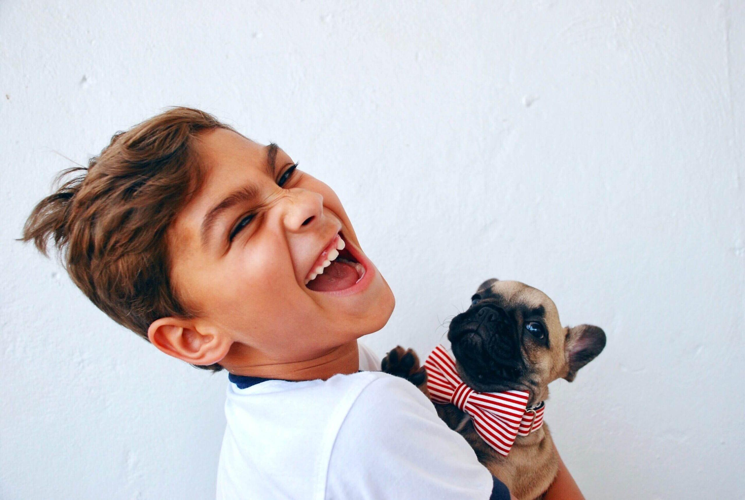 男の子が子犬を抱っこして喜んでいる写真